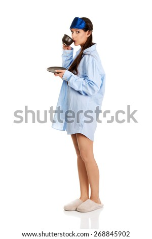Morning woman in big shirt and slippers drinking coffee. - stock photo