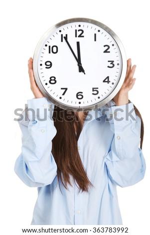 Morning woman in big shirt hiding behind clock. - stock photo