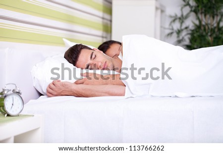 Morning , young couple sleeping together in bed - stock photo