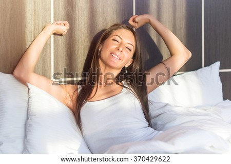 Morning Young woman waking up stretching her arms lying in bed. - stock photo