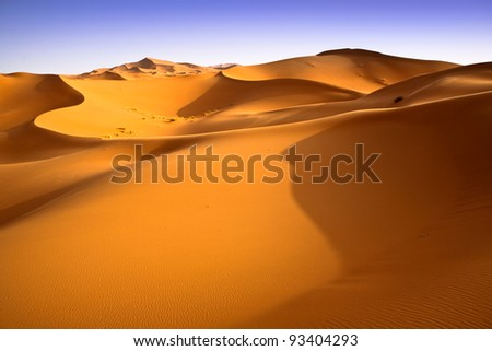 Moroccan dunes landscape with blue sky. Desert background. - stock photo