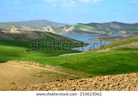 Moroccan landscape with green fields, lake and Atlas mountains on background - stock photo