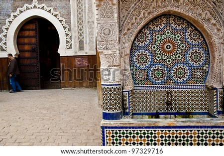 Moroccan mosque entrance with man coming in to pray - stock photo