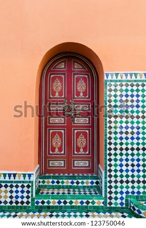 Moroccan painted exterior arched wooden door in red with floral designs and ornate hardware.  Location: Marrakech, Morocco - stock photo