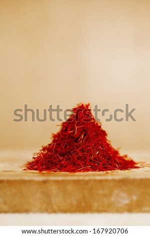 moroccan saffron treads in pile, on wood, shallow dof - stock photo
