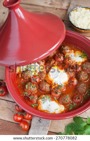 Moroccan tagine of lamb with kefta (meatballs), tomatoes and eggs on a wooden table, selective focus