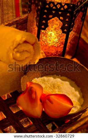 Moroccan-themed spa towel and bath salts on a tray. - stock photo