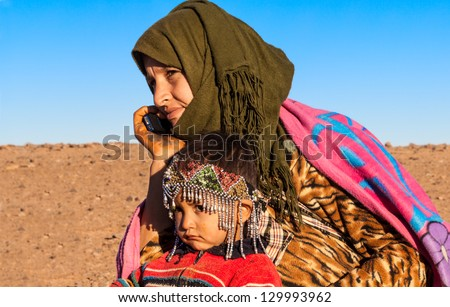MOROCCO-DEC 28: An unidentified nomad mother on a cell phone in the Sahara desert  on Dec. 28, 2012 in Morocco. The telecom regulator ANRT reports mobile penetration in Morocco at more than 110%. - stock photo