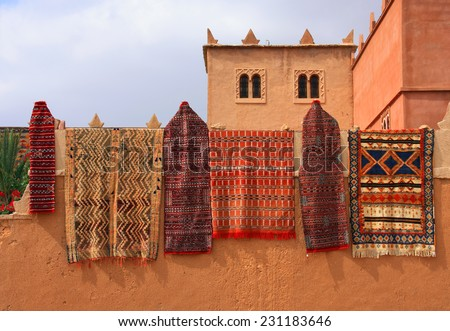 Morocco, Marrakesh, typical colourful Moroccan Berber carpets hanging on display from an adobe wall. - stock photo