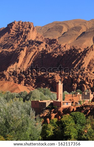 Morocco, Ouarzazate district, Dades Valley, Old village mosque minaret and adobe houses surrounded by lush vegetation and dramatical rock formations in the background  - stock photo