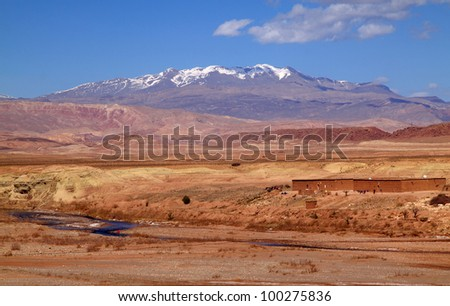 Morocco Ouarzazate -  panorama of the river valley between Ouarzazate and Ait Ben Haddou in the late afternoon sunshine with snow covered peaks of the Atlas Mountains in the background - stock photo