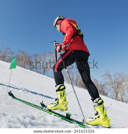 MOROZNAYA MOUNT, KAMCHATKA, RUSSIA - APRIL 25, 2014: Ski mountaineer climb on skis on mountain. Vertical race ski mountaineering Asian, ISMF, Russian, Kamchatka Championship. - stock photo
