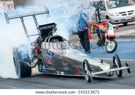 MORRISON, CO - JUNE 15:  D. Dubbin inAlcohol Dragster Car 522 does a burnout during Thunder on the Mountain presented by Grease Monkey at Bandimere Speedway on June, 15, 2013 in Morrison, Co.  - stock photo