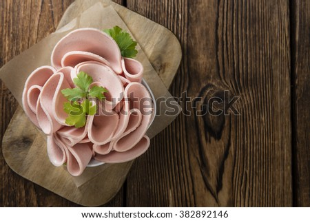 Mortadella Slices (selective focus) on an old wooden table - stock photo
