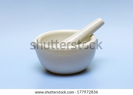 Mortar and pestle on light blue background.