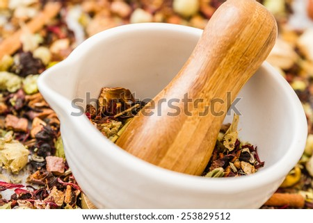 Mortar and pestle set with herbal tea on white wooden background - stock photo