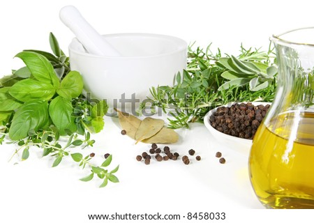 Mortar and pestle with fresh herbs, spices and virgin olive oil, ready for grinding.  Includes basil, rosemary, thyme, oregano, sage, mint, parsley and bay leaves. - stock photo