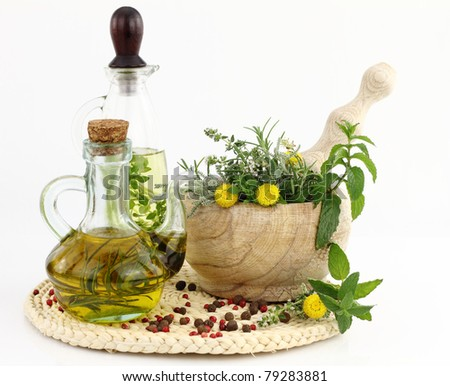 Mortar and pestle with herbs and bottles of olive oil - stock photo