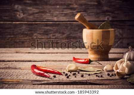 Mortar and pestle with pepper and spices on wooden table - stock photo
