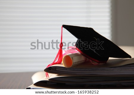 mortar board on stack of files - stock photo