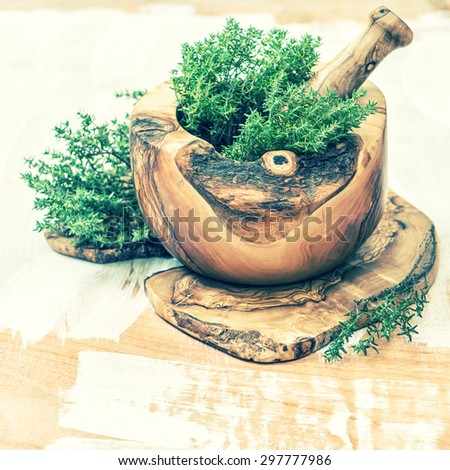 Mortar with fresh thyme herb. Olive wood kitchen tools. Healthy food ingredients. Vintage style toned picture - stock photo