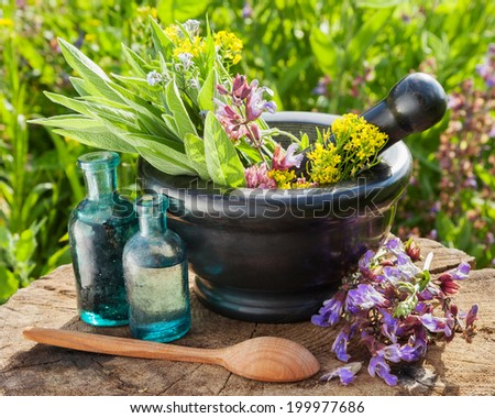 mortar with healing herbs and sage, glass bottle of essential oil outdoors - stock photo