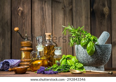 Mortar with herbs and oil on wooden table - stock photo