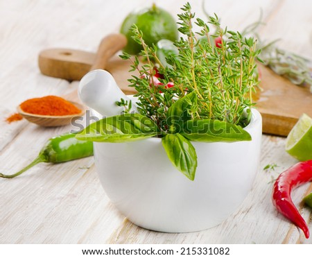 Mortar with  herbs and red  peppers on a wooden table. Selective focus