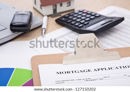 mortgage application form with laptop, phone; calculator and house - stock photo