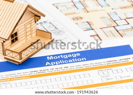Mortgage application with model house and drawing - stock photo