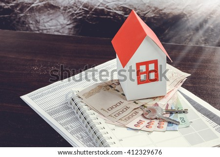 mortgage, investment, real estate and property concept.  close up of home model, Thai money and house keys - stock photo
