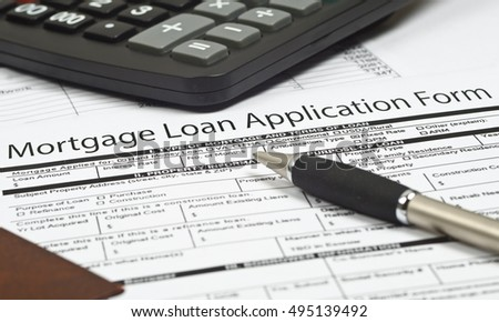 mortgage loan application form, the  pen and a calculator.
