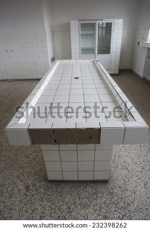 mortuary slabs at old abandoned hospital - stock photo