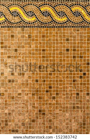 Mosaic in ancient style stacked with tiny brown, yellow, blue tiles. Background with mosaic tiles with ornament. - stock photo