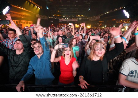 MOSCOW - APR 05, 2014: A crowd of happy young people with their hands raised at the disco in Stadium Live - stock photo
