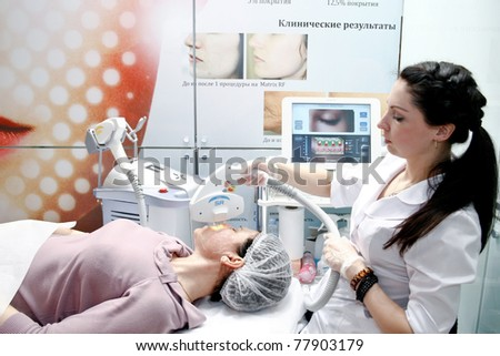 MOSCOW - APRIL 14: Beautician performs a procedure at the international exhibition of professional cosmetics and beauty salon equipment INTERCHARM on April 14, 2011 in Moscow - stock photo