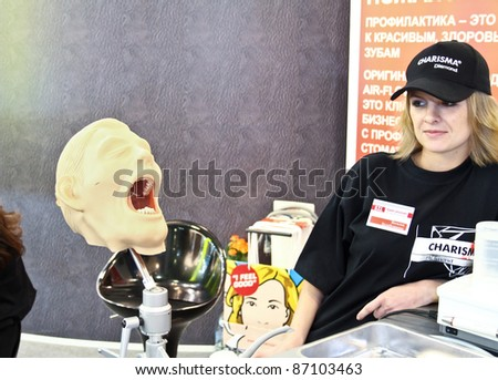 MOSCOW - APRIL 27: Girl looks on the head dental manikin at the international exhibition of the dental professionals and industry on April 27, 2011 in Moscow - stock photo