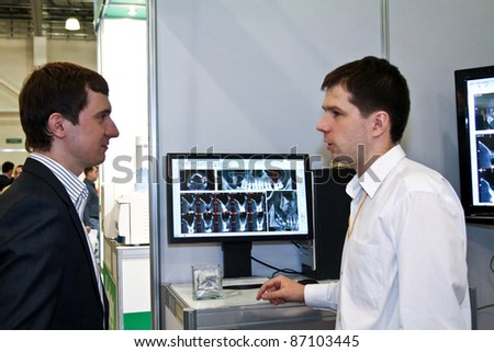 MOSCOW - APRIL 27: Man talk about dental x-rays at the international exhibition of the dental professionals and industry on April 27, 2011 in Moscow - stock photo
