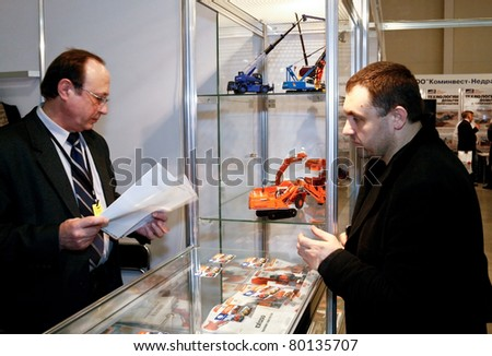 MOSCOW - APRIL 13: Men discuss mining equipment at the international exhibition of  the Mining and Processing of Metals and Minerals, MiningWorld on April 13, 2011 in Moscow - stock photo