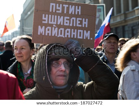 "MOSCOW - APRIL 13, 2014: Opposition meeting in protection of freedom of mass media ""March of truth"". Woman with the poster. Text: ""Putin was hurt by the Maidan"""