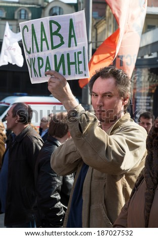 "MOSCOW - APRIL 13, 2014: Opposition meeting in protection of freedom of mass media ""March of truth"".Man with placard ""Glory to Ukraine!"""