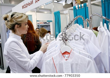 MOSCOW - APRIL 14: Unidentified girl chooses gown at the international exhibition of professional cosmetics and beauty salon equipment INTERCHARM on April 14, 2011 in Moscow