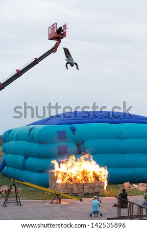 MOSCOW - AUG 25: Man jumping from a height into the burning box on Festival of art and film stunt Prometheus in Tushino on August 25, 2012 in Moscow, Russia. The festival was organized in 1998. - stock photo
