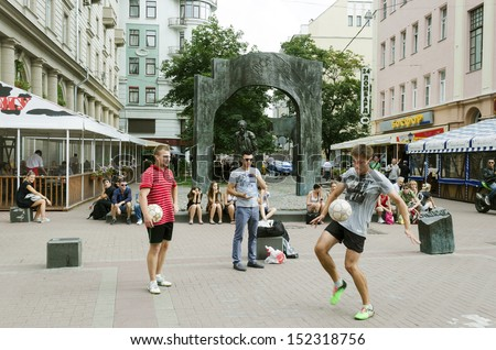Moscow - Aug,7: Young people play with a soccer ball at the monument to Boris Okudzhava on Arbat street on August,7 2013 in Moscow, Russia - stock photo