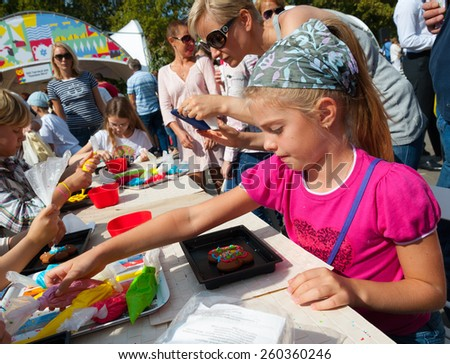 MOSCOW - AUGUST 24: Children making cakes during celebration Apple Feast Day in VDNKH Park on August 24, 2014 in Moscow. Savior of Apple Feast Day is an Eastern Slavic folk holiday. - stock photo