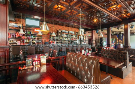"MOSCOW - AUGUST 2014: Interior of a luxury disco bar restaurant with a banquet hall and cafeteria - ""BrownBar"". Large restaurant bar with wooden tables and leather sofas"
