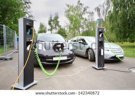 MOSCOW - AUGUST 18: Two electric cars recharged at electrical charging at festival Ekofest 2012 on banks of Stroginsky gulf, on August 18, 2012 in Moscow, Russia. - stock photo