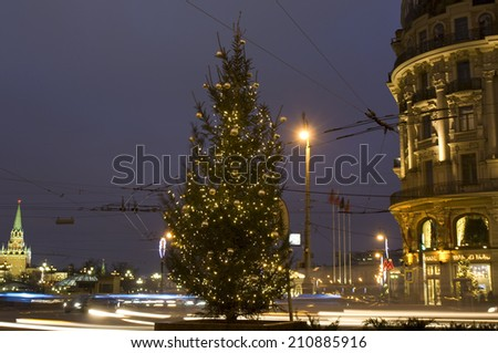 "MOSCOW - DECEMBER 26, 2013: Christmas tree on cross of Tverskaya street and Manezhnaya square near hotel ""National"" and Kremlin tower."