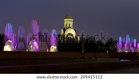 MOSCOW - DECEMBER 25, 2013: electric fountain - illumination to Christmas and New Year holidays - and St. George chruch in historical memorial Poklonnaya hill. - stock photo