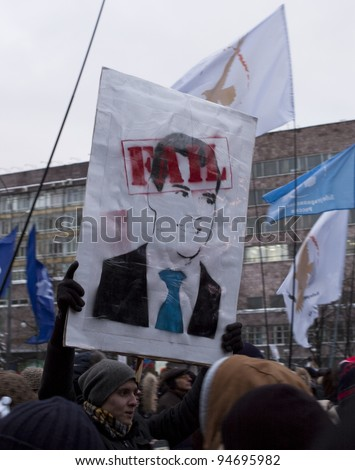"MOSCOW - DECEMBER 24: Man, holding poster with President Medvedev and the inscription: ""Fail"". Protest against election results. December 24, 2011 in Moscow, Russia. - stock photo"